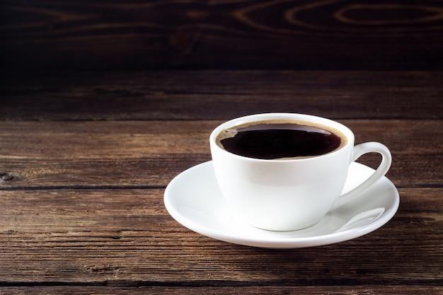 木製のテーブルにブラックコーヒーと白いカップ Premium写真