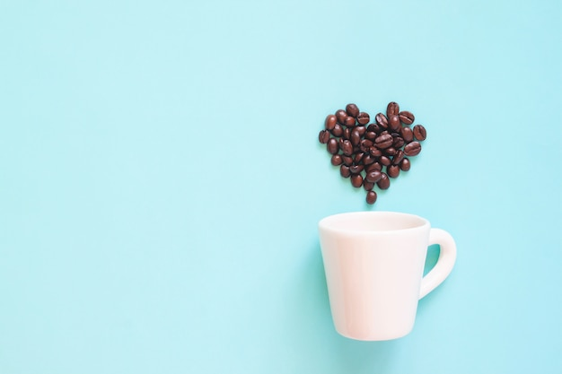 White cup with coffee beans arranged in heart shape on pastel colour background Premium Photo
