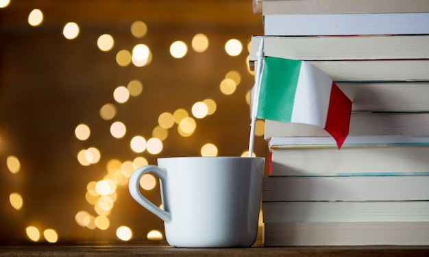 White cup with italy flag near books Premium Photo