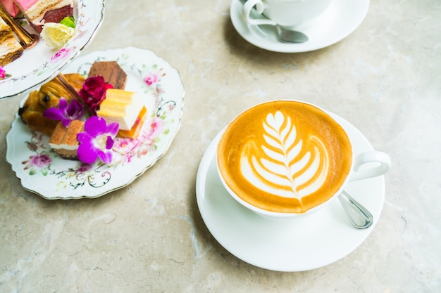 White cup with latte coffee and cake Free Photo