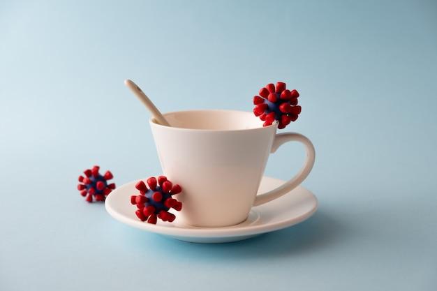 Белая чашка с моделями вируса ковид-19. эпидемический коронавирус. риск заражения концепцией covid-19. Premium Фотографии