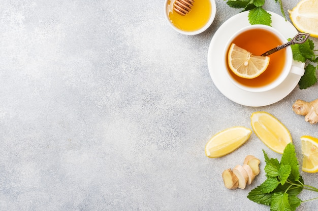 White cup with natural herbal tea ginger lemon mint and honey. Premium Photo
