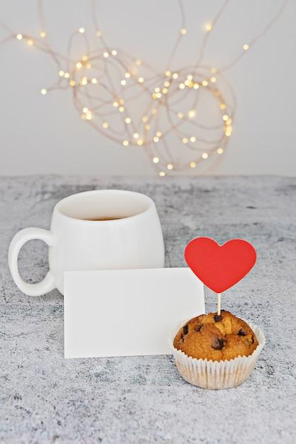 バレンタインチョコレートキャンディの赤いハートとマフィンホワイトカップ Premium写真