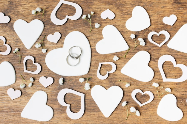 White cut out heart shapes with baby's-breath flowers on wooden desk Free Photo