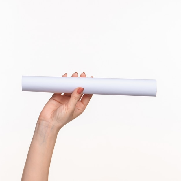 白い背景の上の女性の手の小道具の白い円柱 無料写真