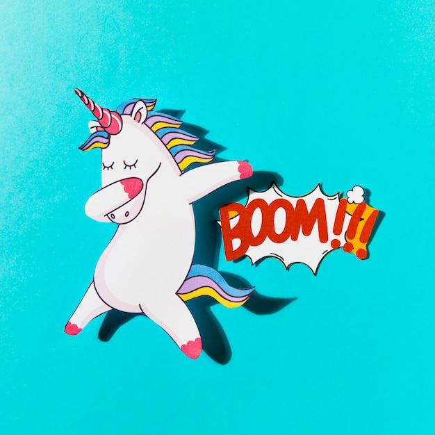 White dabbing unicorn with boom comic text on blue backdrop Free Photo