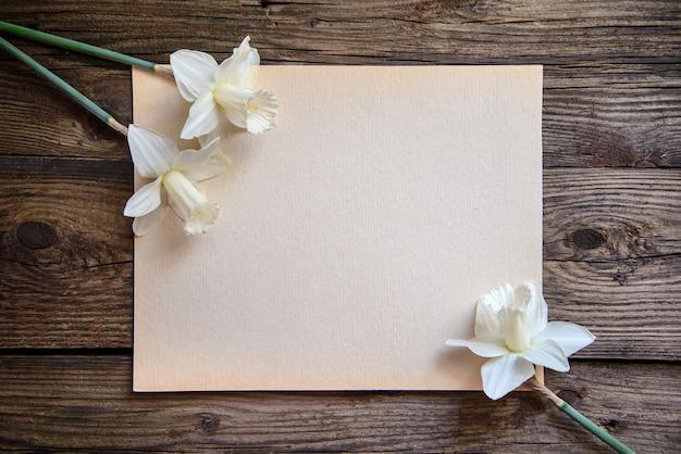 木製の背景に紙に白い水仙 Premium写真