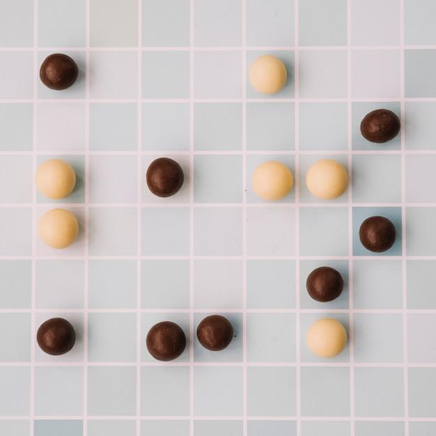 White and dark chocolate balls on checkered backdrop Free Photo