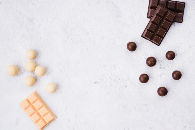 White and dark chocolate bar and balls on white rough background Free Photo