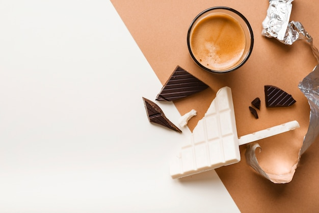 White and dark chocolate bar with coffee glass on dual background Free Photo