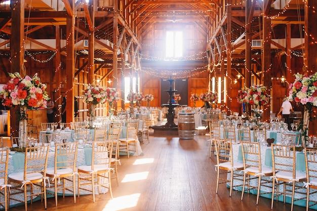 White daylight illuminates a wooden hangar prepared for a wedding Free Photo