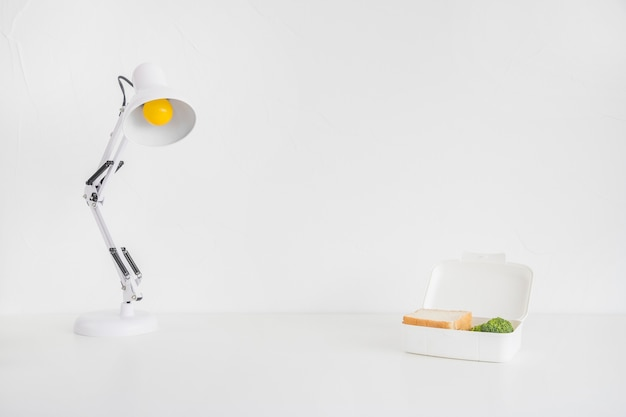 White desk lamp and lunch box Free Photo