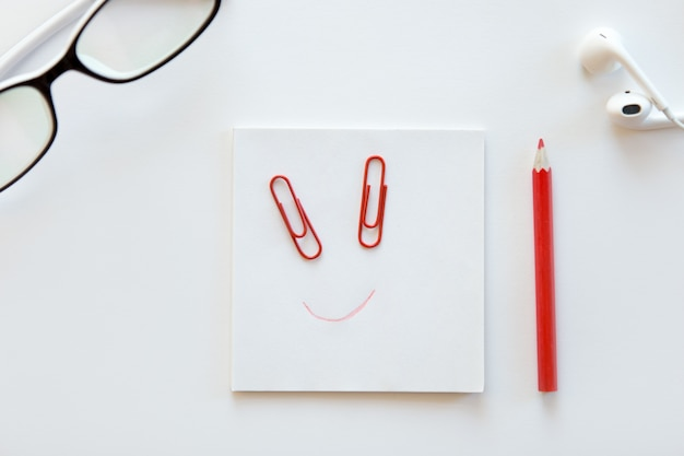 White desk with paper block, a drawn smile on it Free Photo