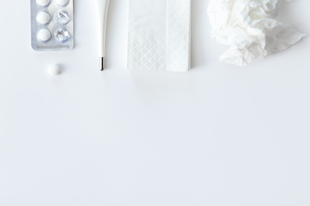 White desk with round pills, thermometer, paper crumpled napkin Free Photo