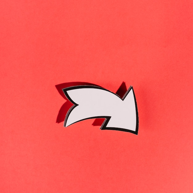 White directional arrow on red background Free Photo