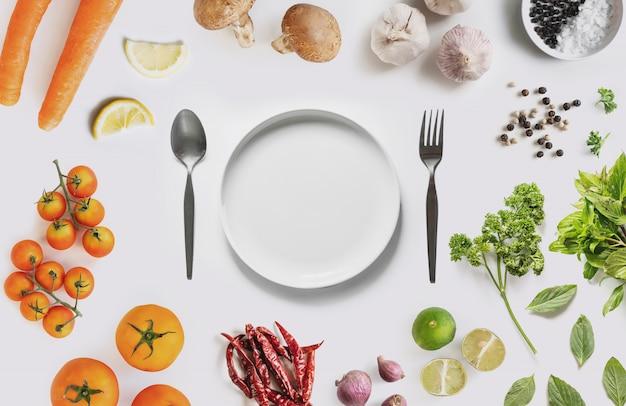有機野菜、ハーブ、スパイス、白い背景の上に白い皿サラウンド Premium写真