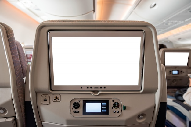White display screen with joystick on rear seat in airplane Premium Photo