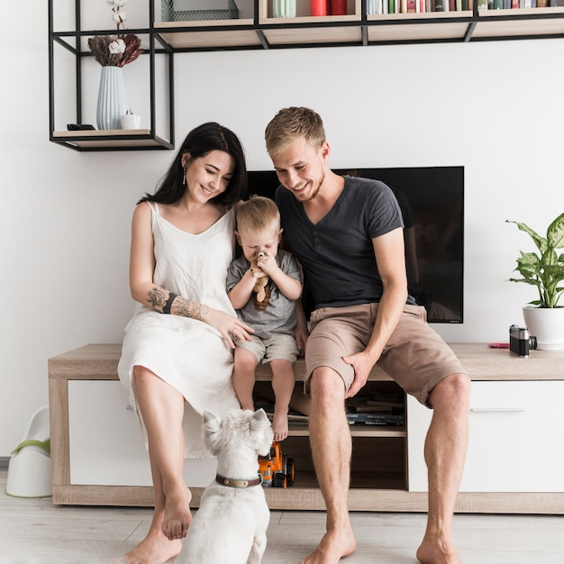 White dog looking at smiling young couple sitting with their son in front of television Free Photo