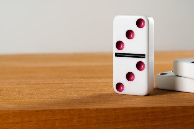 Белая кость домино стоя на конце деревянного стола вверх Premium Фотографии