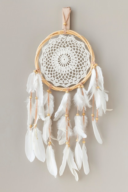 White dream catcher hanging on a off white wall Free Photo