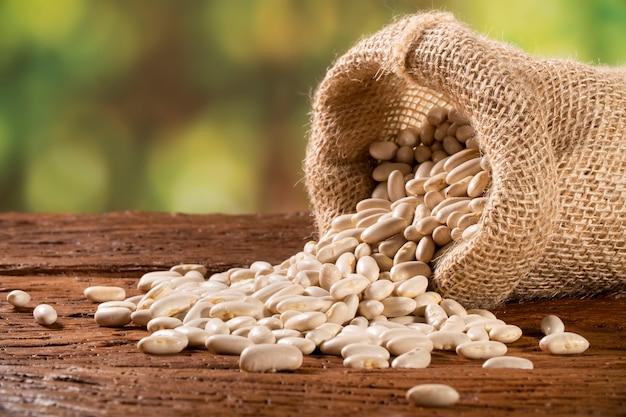 木製のテーブルの黄麻布の袋に白い乾燥インゲンマメ、マメ科植物の豆の概念のヒープ。 Premium写真
