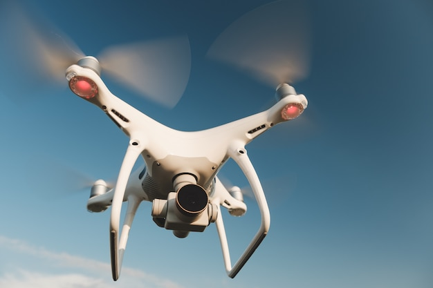 White drone hovering in a bright blue sky Free Photo