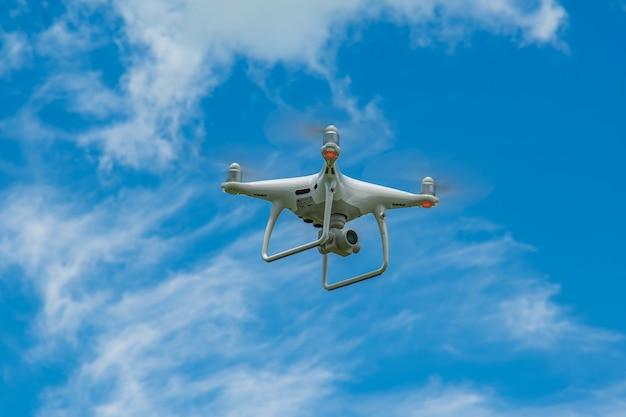 Белый дрон, парящий в ярко-синем небе, радиоуправляемый вертолет Premium Фотографии