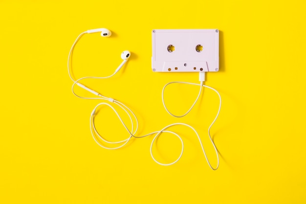 White ear phone connected to cassette tape on yellow background Free Photo