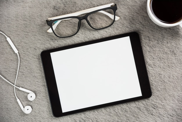 White earphone; eyeglasses; coffee cup and blank screen digital tablet on gray desk Free Photo