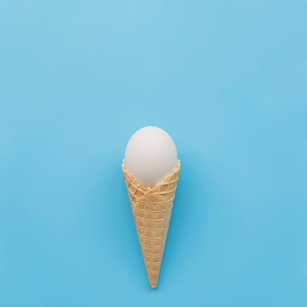 White egg in waffle horn on blue background Free Photo