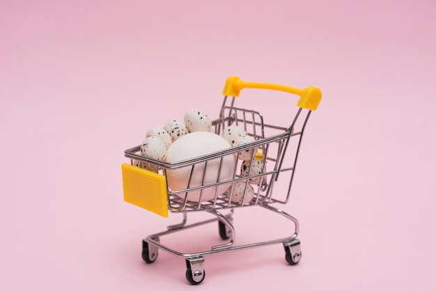 White eggs in grocery cart on table Free Photo