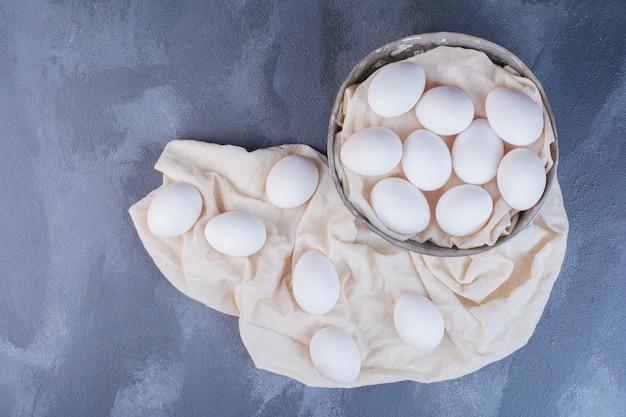 金属製のカップとタオルの上に白い卵 無料写真