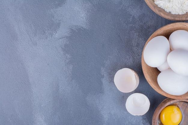 周りに黄色い卵黄が付いている木製のカップの白い卵。 無料写真