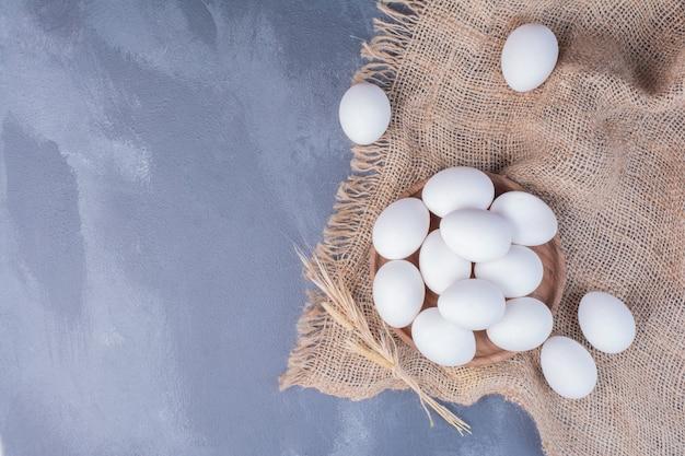 黄麻布の木製の大皿に白い卵 無料写真