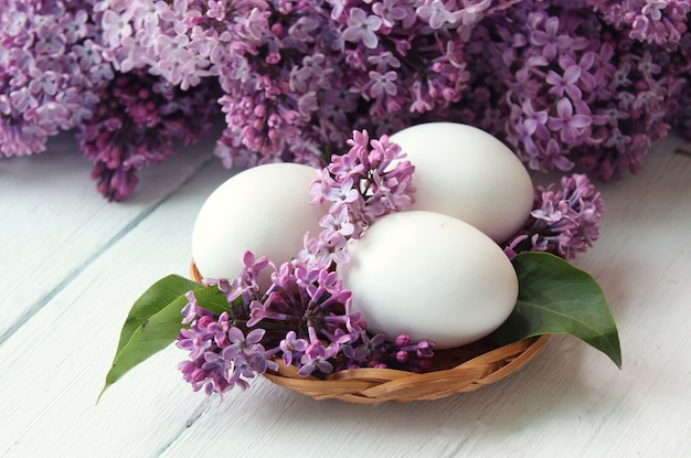White eggs inside a lilac basket and a bouquet around. Free Photo