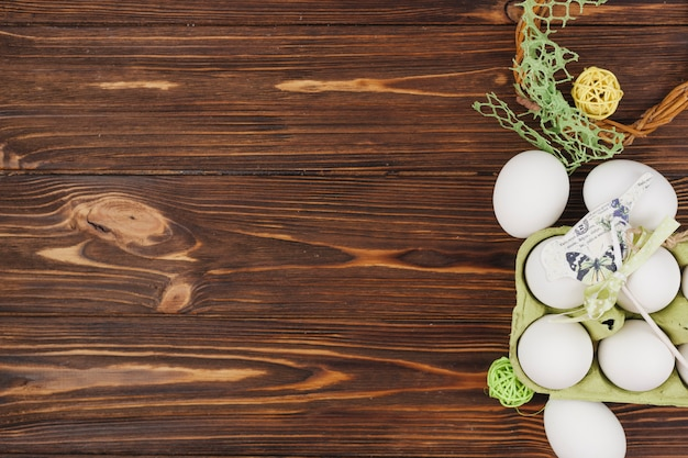 White eggs in rack with small bird on table Free Photo