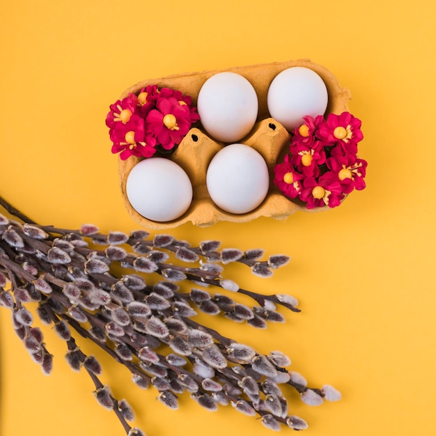 White eggs in rack with willow branches on table Free Photo