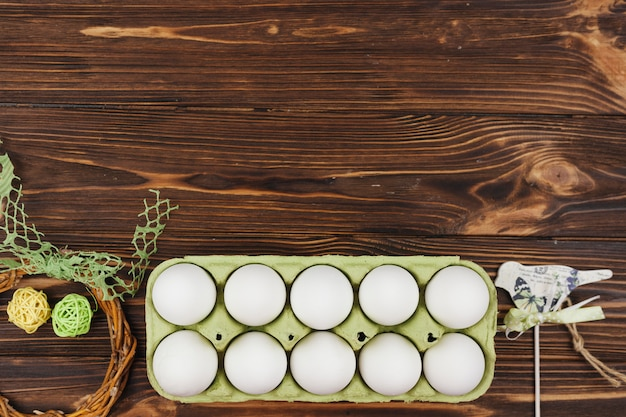 White eggs in rack on wooden table Free Photo