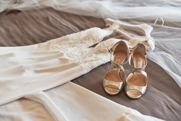 White elegant wedding dress and shoes lying on the bed. Premium Photo