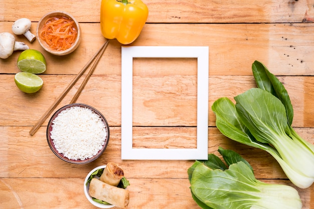 White empty border frame with bell pepper; bokchoy; rice; lemon; mushroom and carrot on wooden desk Free Photo