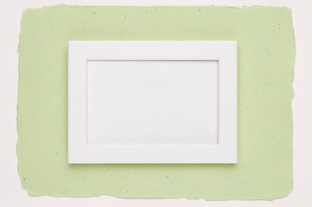 White empty frame on green paper background Free Photo