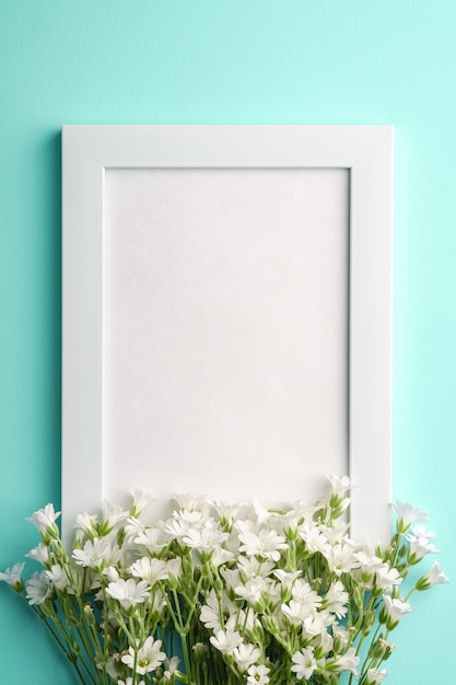White empty photo frame with mouse-ear chickweed flowers on blue background, top view copy space Pre