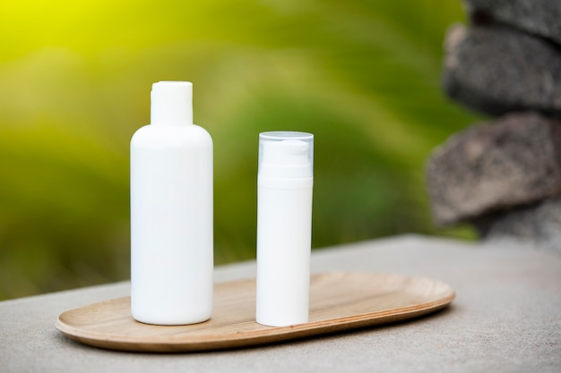 White empty tube of skincare bottle on bamboo plate Free Photo