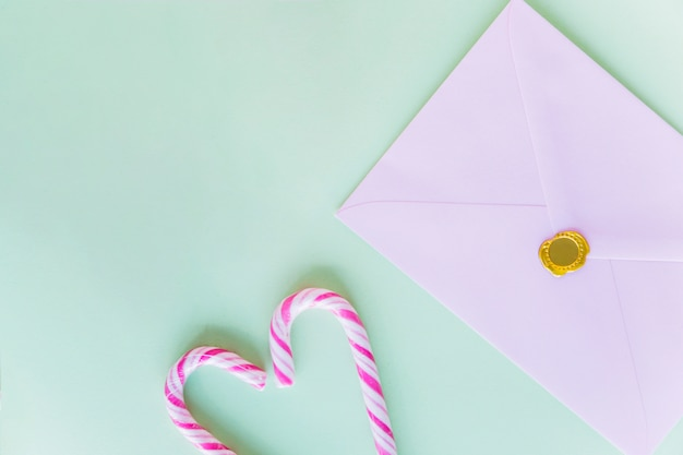 White envelope with candy canes on table Free Photo