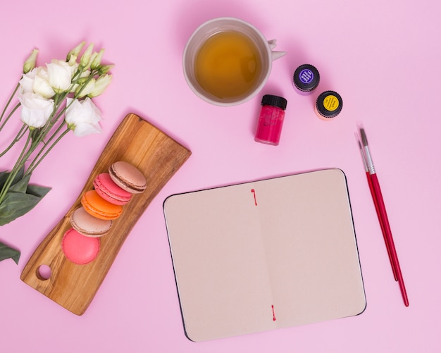 White eustoma flower; macaroons; herbal tea cup; paintbrush and paint bottles near the blank notepad against pink background Free Photo