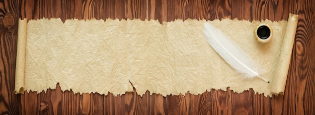 White feather with old paper on the table, panoramic view Premium Photo