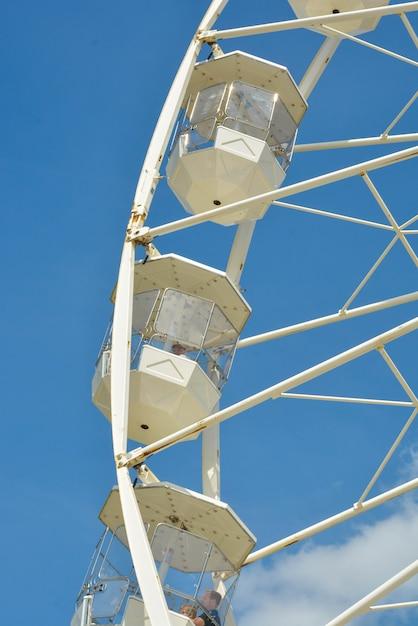White ferries wheel of the amusement park in the blue sky Premium Photo