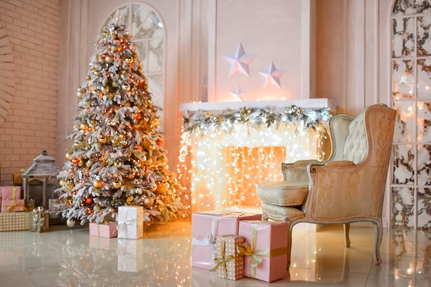 White fireplace decorated with yellow garland and christmas tree standing by it Free Photo
