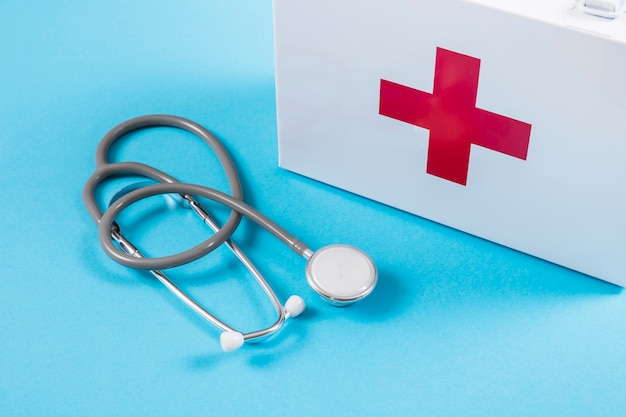 White first aid kit and stethoscope on blue background Free Photo