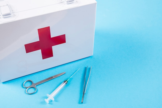 White first aid kit with scissor; syringe and tweezers on blue background Free Photo